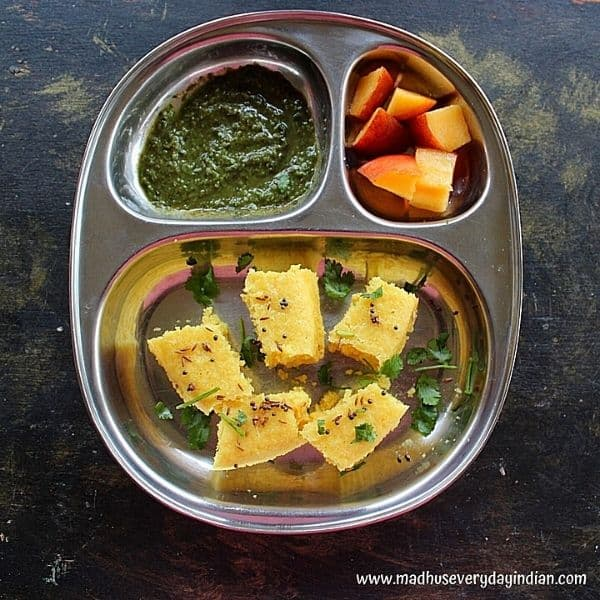 5 pieces of dhokla served with chutney and peaches in a steel plate