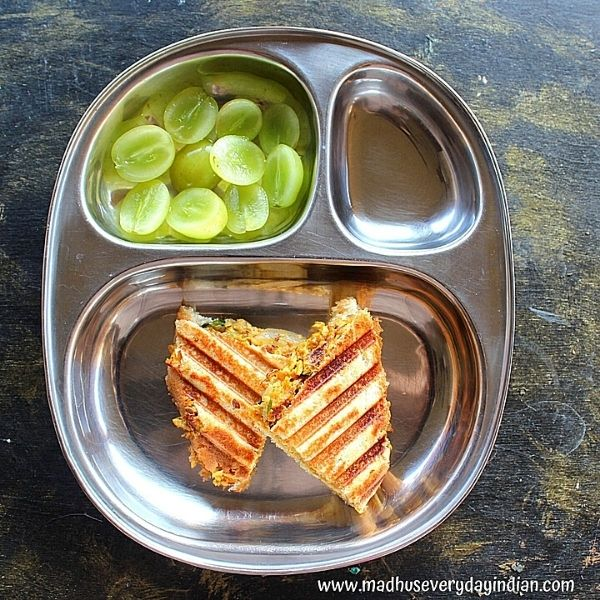 2 egg burji sandwich served with sliced grapes in a steel plate