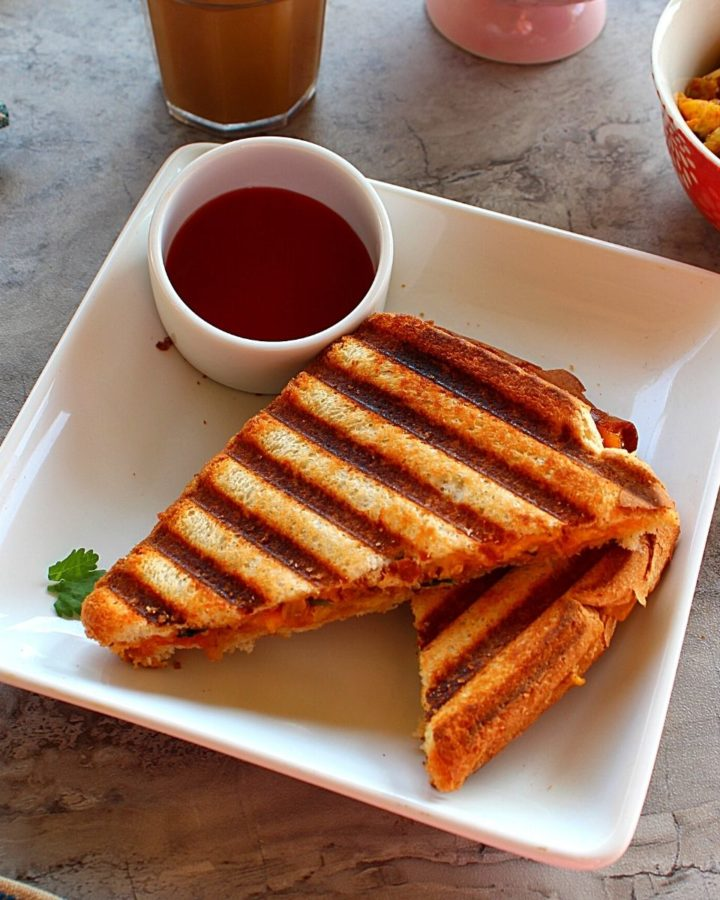 2 pieces of egg burji sandwich served with ketchup, coffee and blueberries