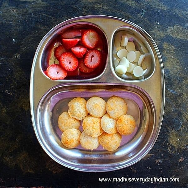 idli drizzled with chutney podi and served with cheese and strawberry