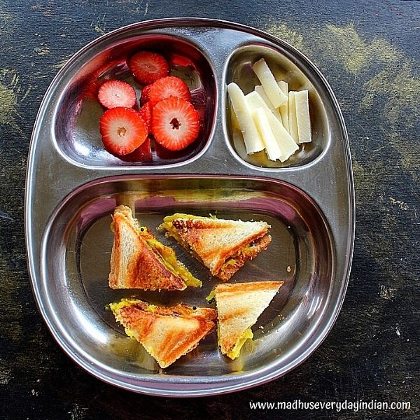 potato sandwich served with strawberry and sliced cheese