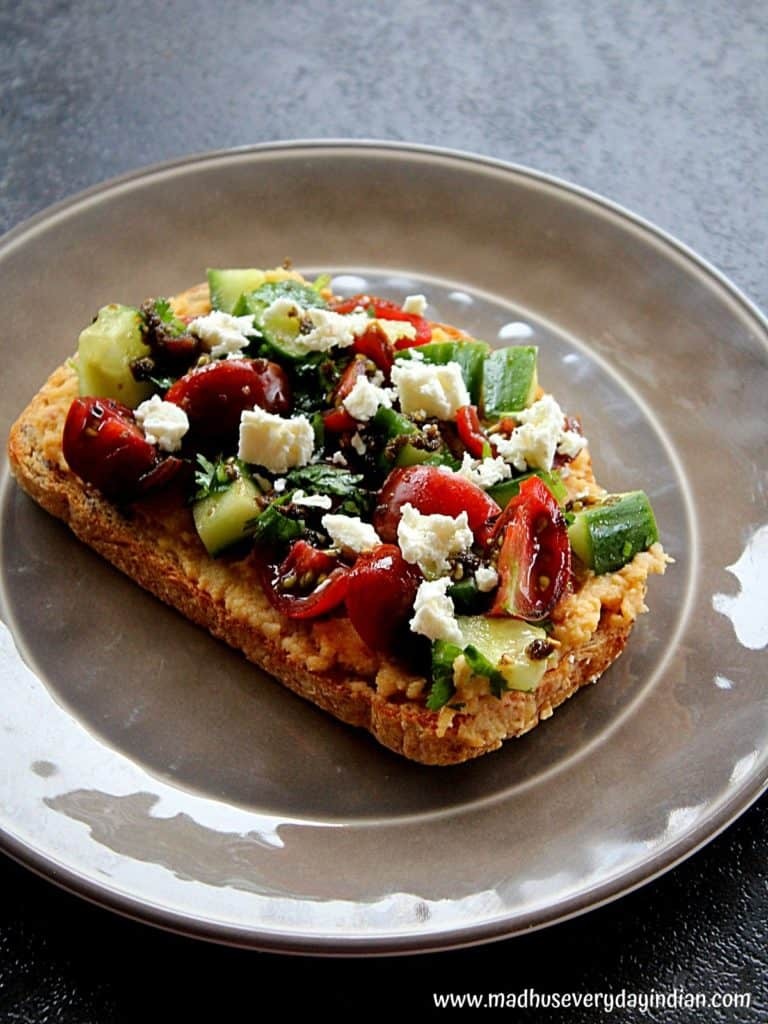 hummus toast topped with vegetables, zaatar and vegan feta cheese