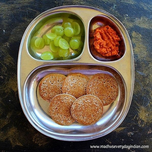 5 mini dosa served with onion chutney and sliced grapes in a steel partition plate