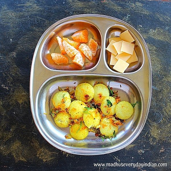 tadka mini idli with orange and cheese served in a partition steel plate