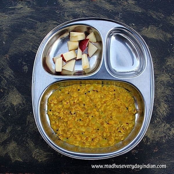 oats upma served with sloced apple served in a steel plate