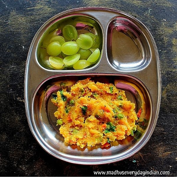 tomato upma served with grapes in a steel plate