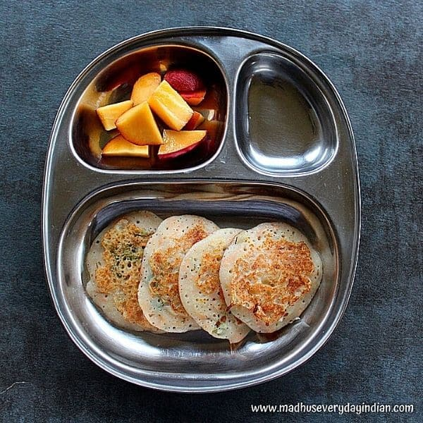 4 mini uttapam served with peaches in a steel partition plate