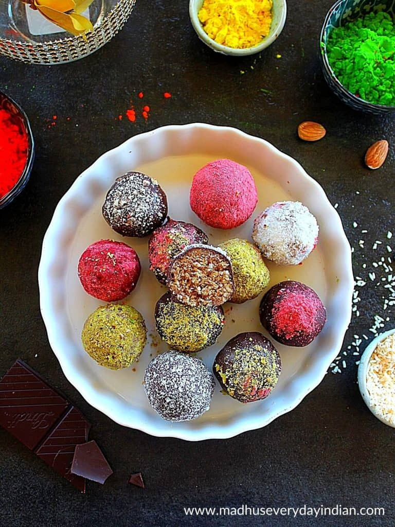 almond truffles sweetened with dates arranged in a white plate with holi colors in the background