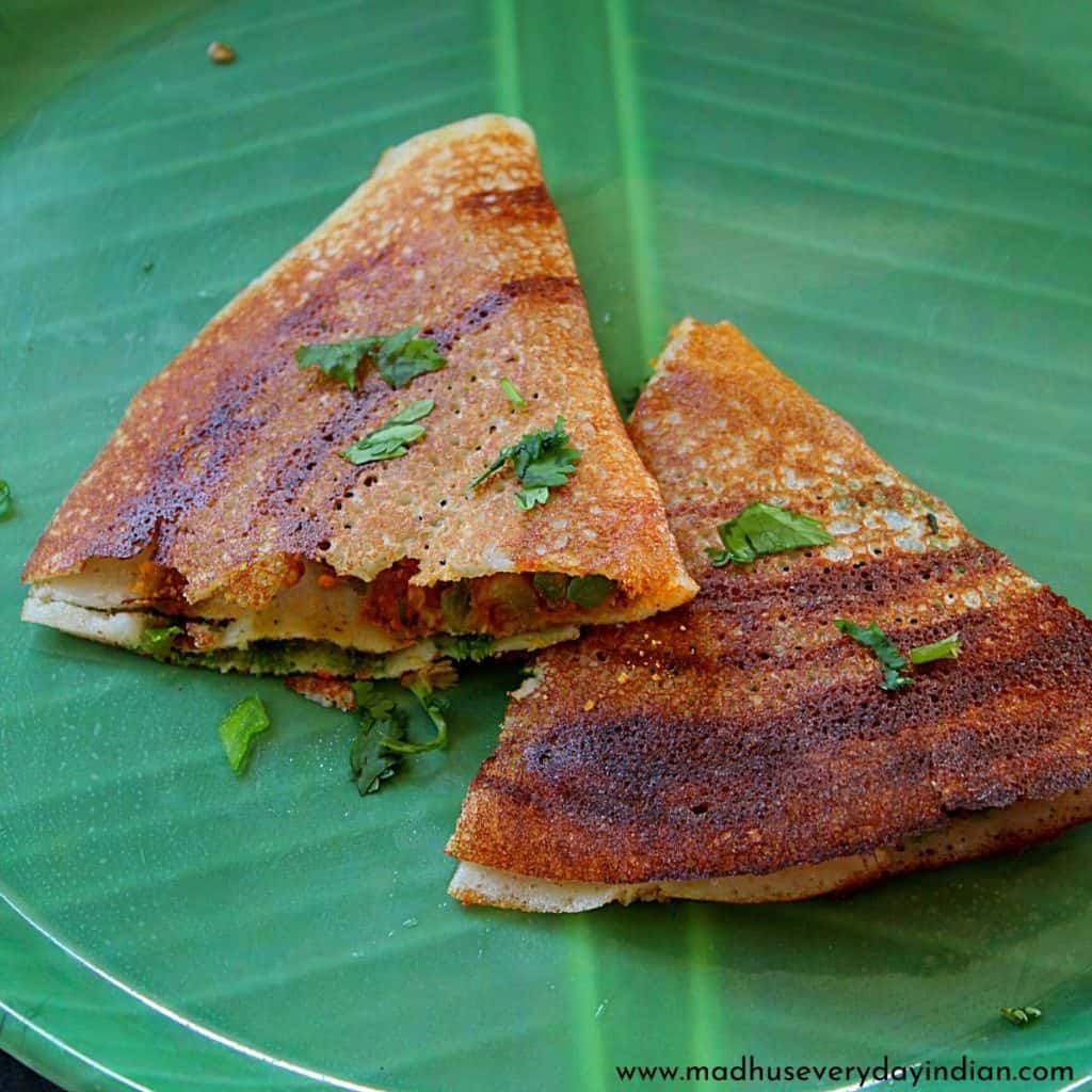 2 pieces of dosa wrap served in a green plate