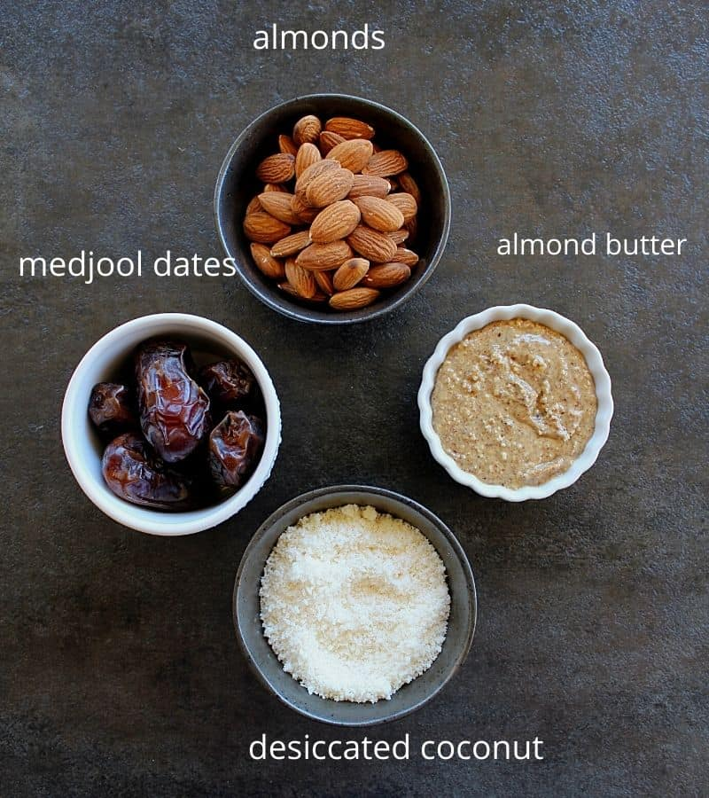 almonds, dates, almond butter and desiccated coconut arranged in 4 bowls