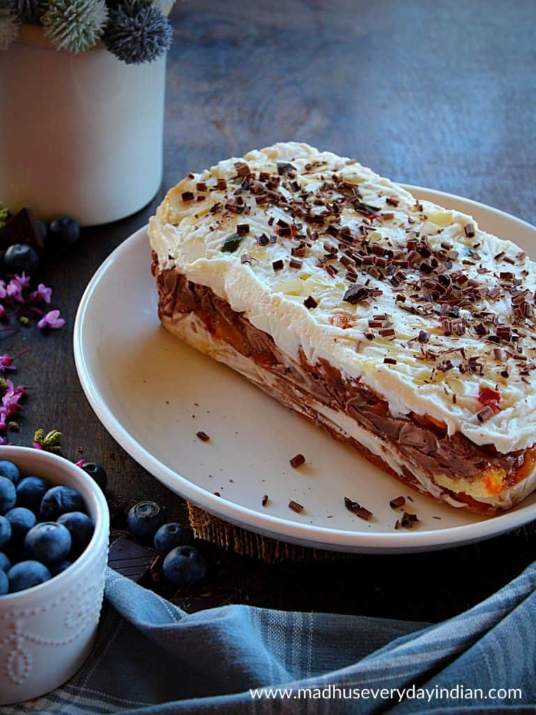 ice cream cake arranged in a white plate with blueberries on the side.