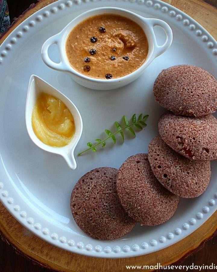 5 ragi idli served in a white plate with ghee and peanut chutney