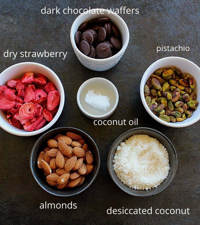 dry strawberry, chocolate, coocnut oil, pistachio, almonds and coconut arranged in bowls