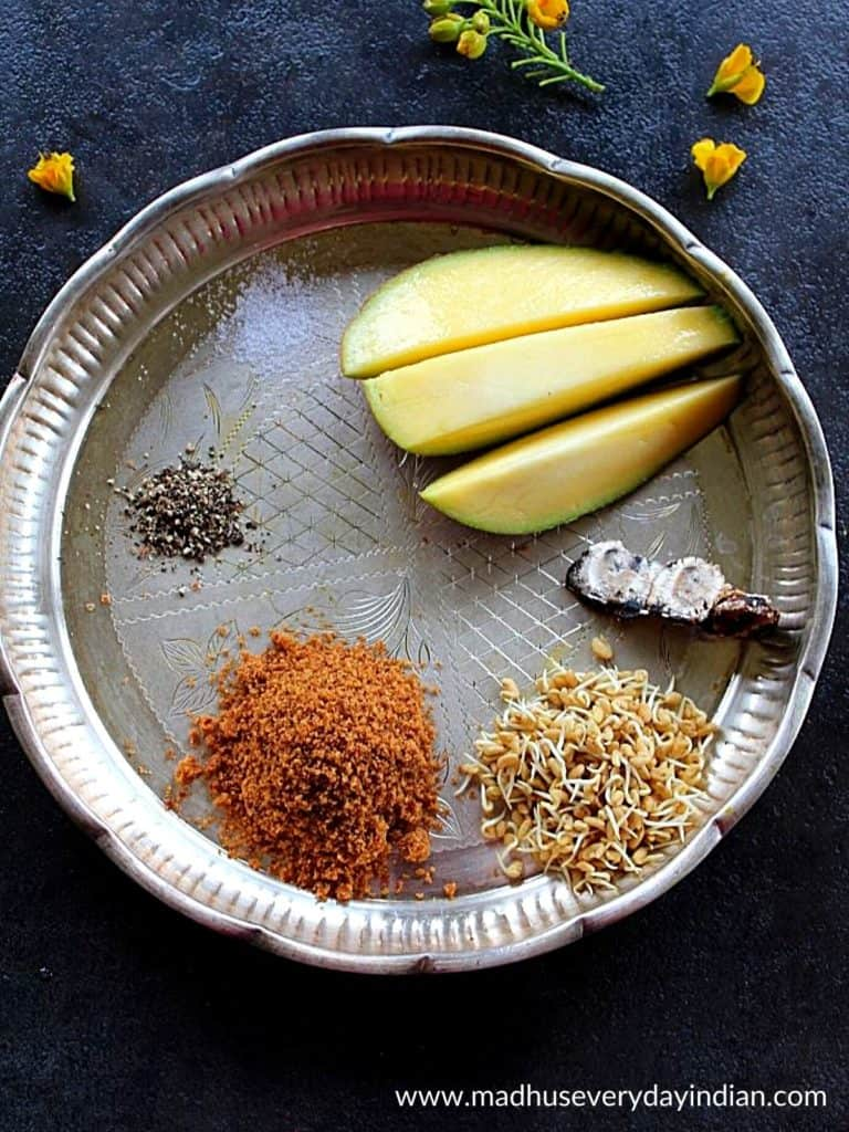 mango, pepper, tamarind, methi and jaggery placed in a sliver plate.