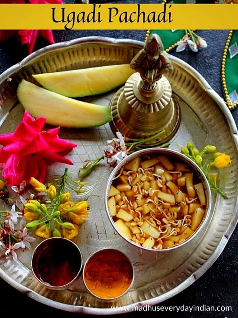 ugadi pachadi served in a sliver plate with banana and flowers.