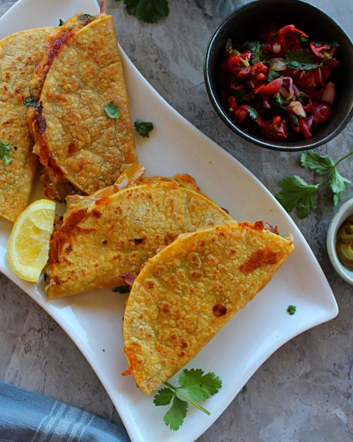 4 indian style potato tacos served in a long white plate served with pico de gallo and garnished with cilantro.