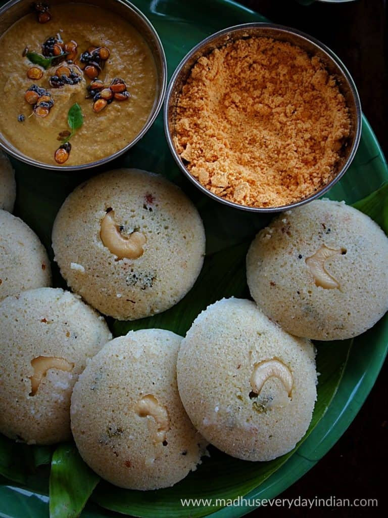 jowar idli served in a green plate with peanut chutney and chutney podi