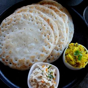 5 poha dosa served in a cast iron pan with potato fry and chutney.