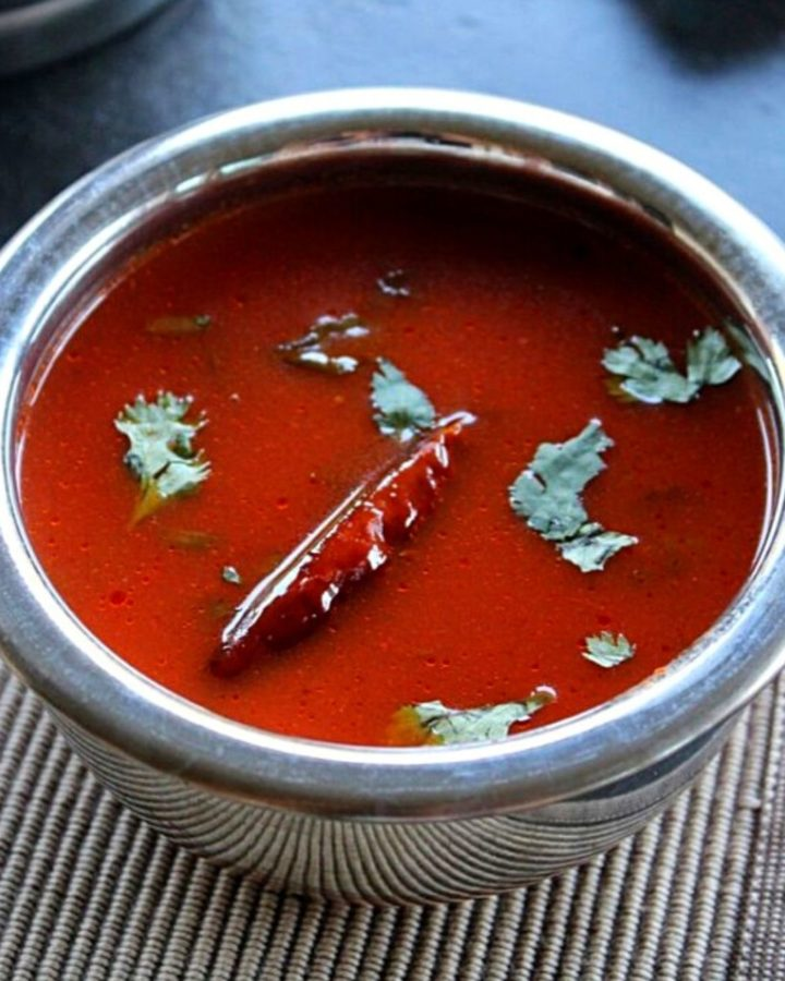 tomato paste rasam served in a steel bowl garnished red chili and coriander leaves.
