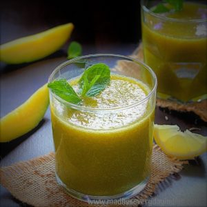 aam paan with pudina served in a glass cup garnished with mint leaves.