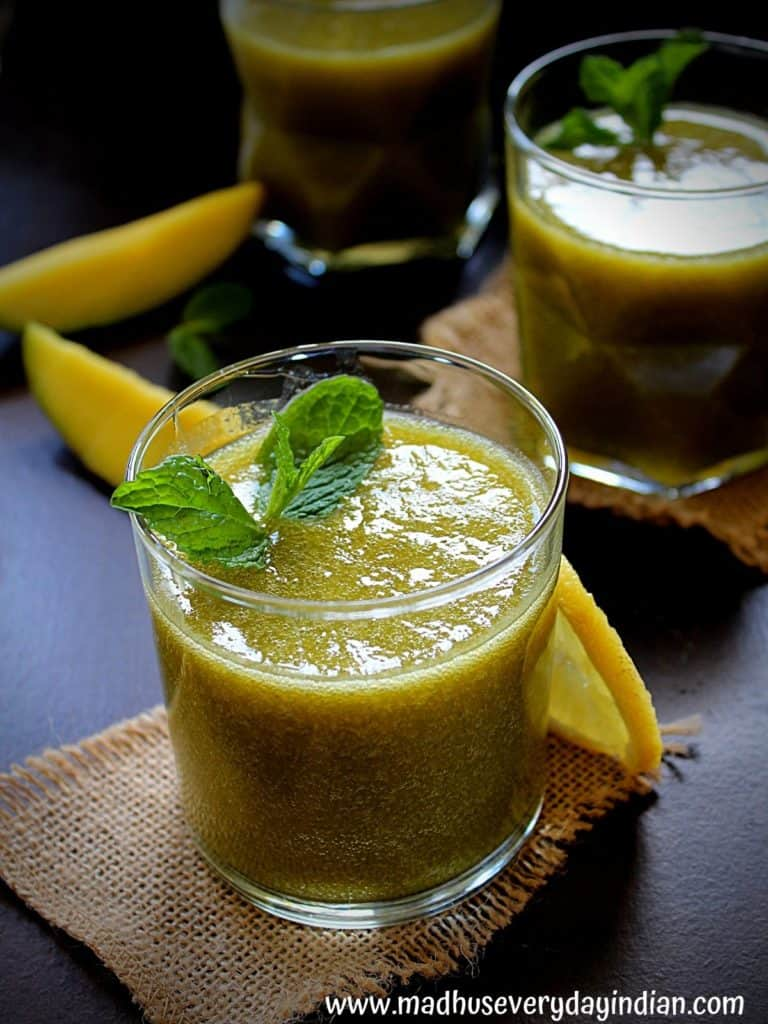 aam panna made with mint and dates served in a glass cup garnished with mint and lemon and mango slices on the side.