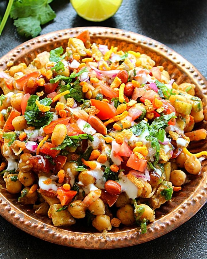 chana chaat served in copper plate served with coriander leaves and lemon slices.