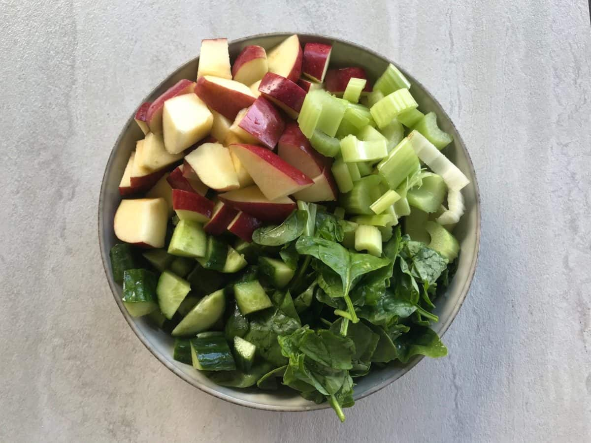 chopped apple, celery, cucumber and spinach in a large plate