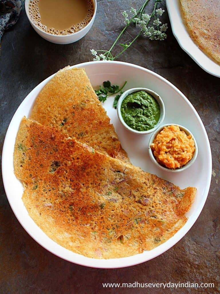 2 instant jowar dosa served with green chutney and onion cg chutney in a white plate.