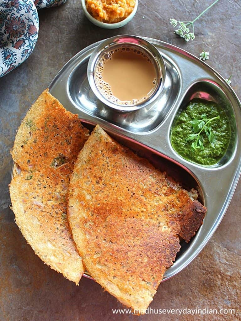 2 jowar dosa served with chutney and coffee in a steel plate