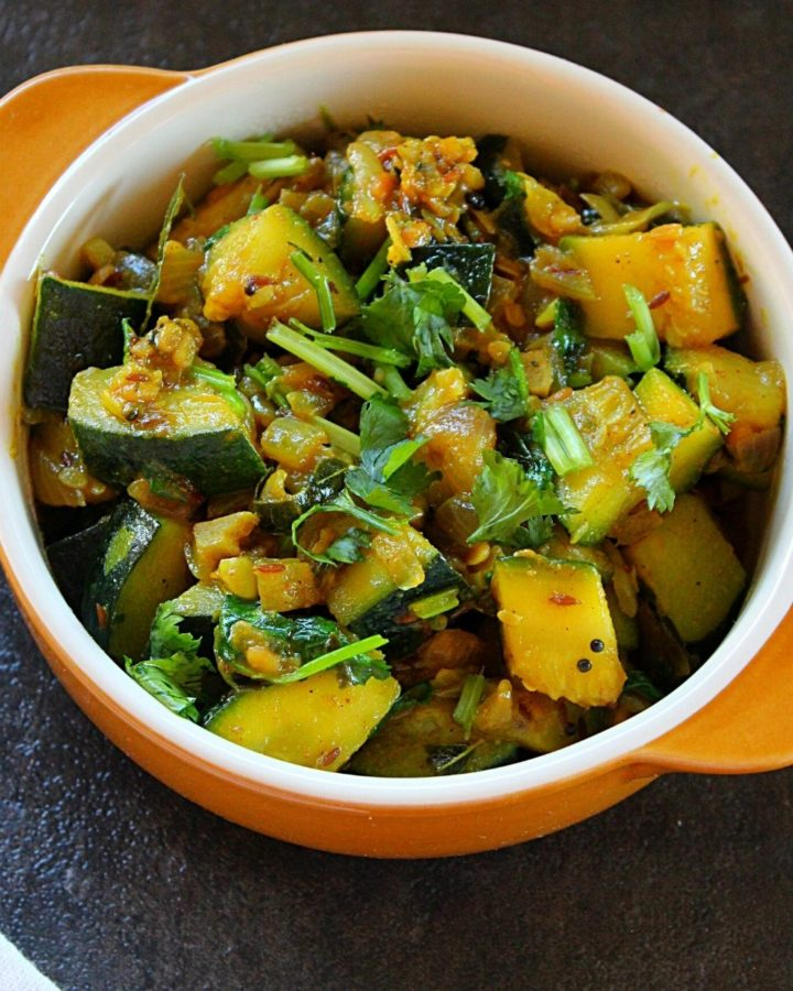 zucchini sabazi served ina yellow bowl garnished with coriander leaves.