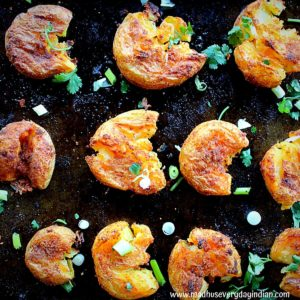 crispy masala smashed potato served in a tray garnished with coriander leaves and spring onion.