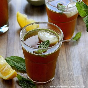 gur ka sharbat served in a glass cup with ice and mint garnished and lemon slices on the side.