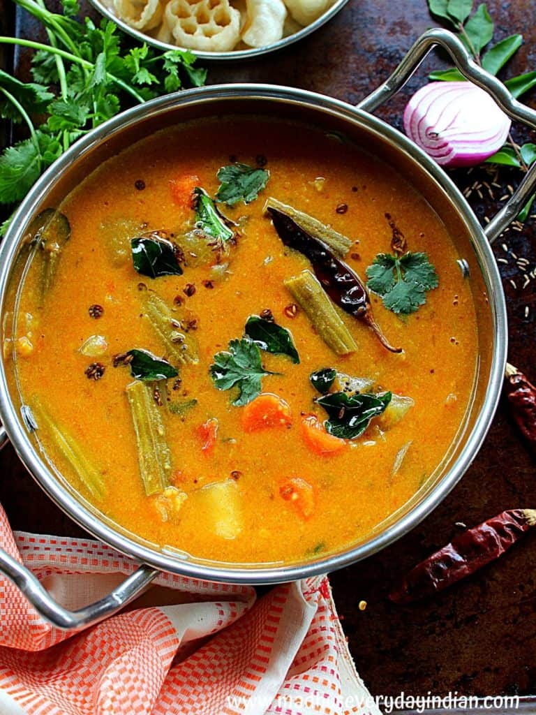 sambar served in a steel kadai garnished with curry leaves and coriander.