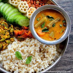 instant pot sambar served with rice, cucumber, veggies and peanuts in a steel plate.