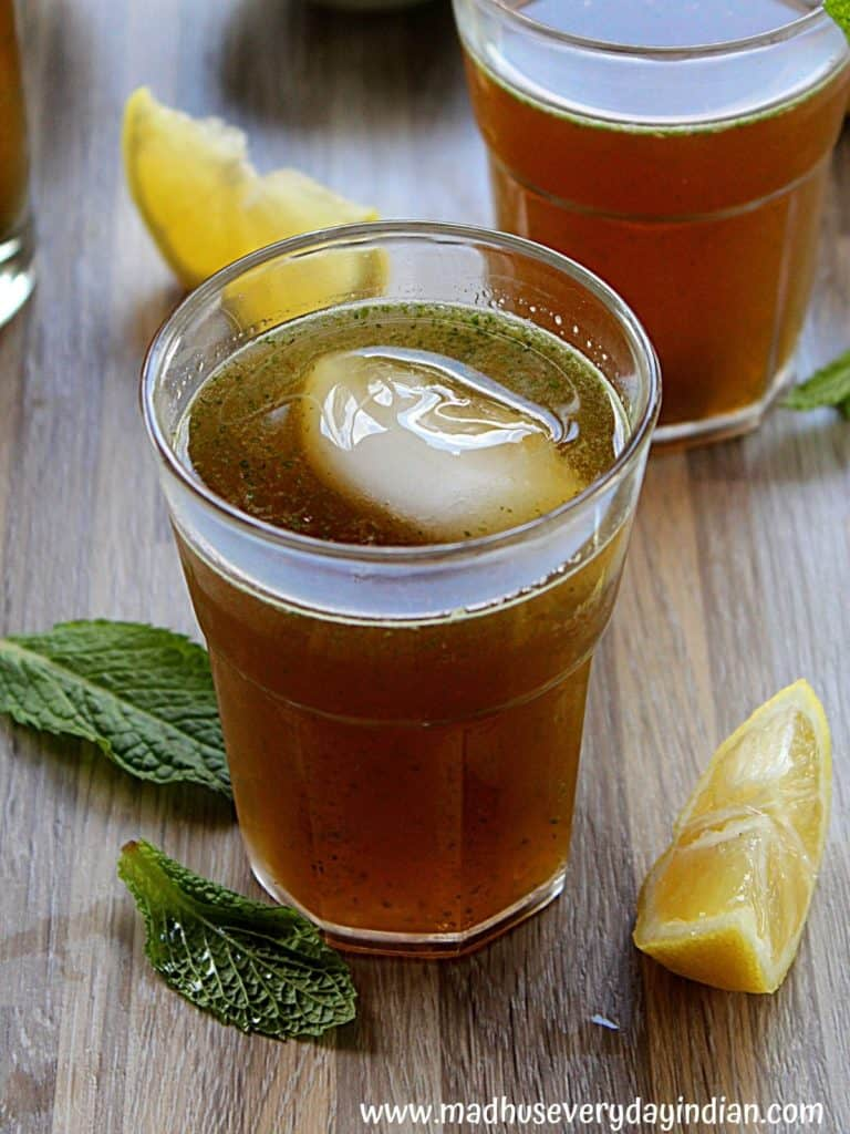 jaggery juice served in a glass cup with ice and mint garnished and lemon slices on the side.