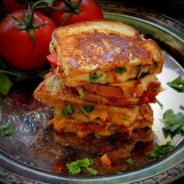 stacked tomato chutney grilled cheese in a metal plate