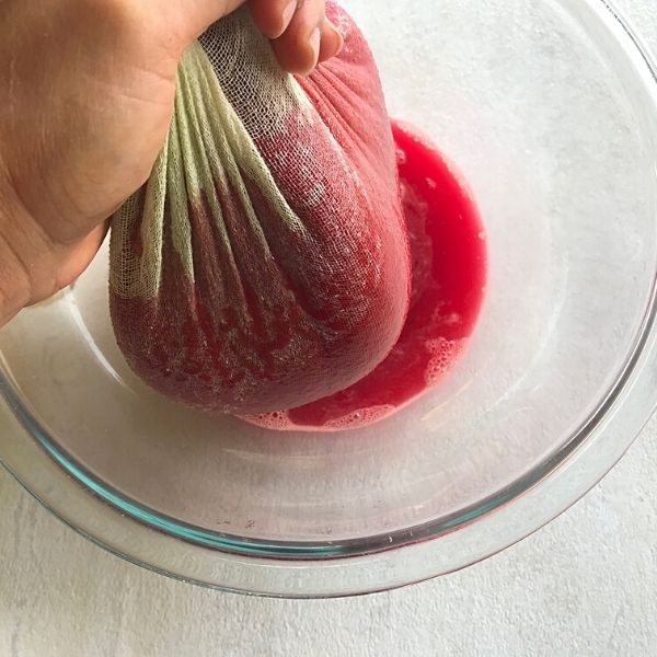 squeezing out the vegetable juice with a cheese cloth.