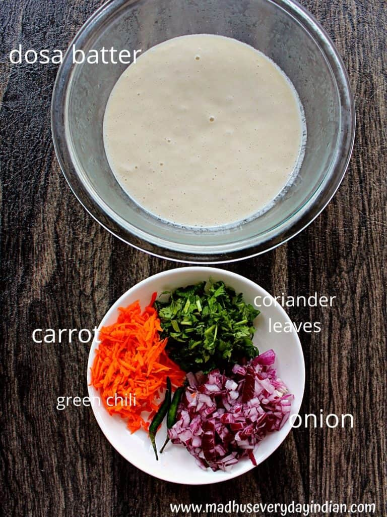 dosa batter, onion, carrot, coriander leaves and green chili in a plate