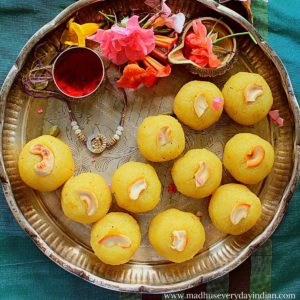 rava kesari ladoo served in a silver plate garnished with flowers