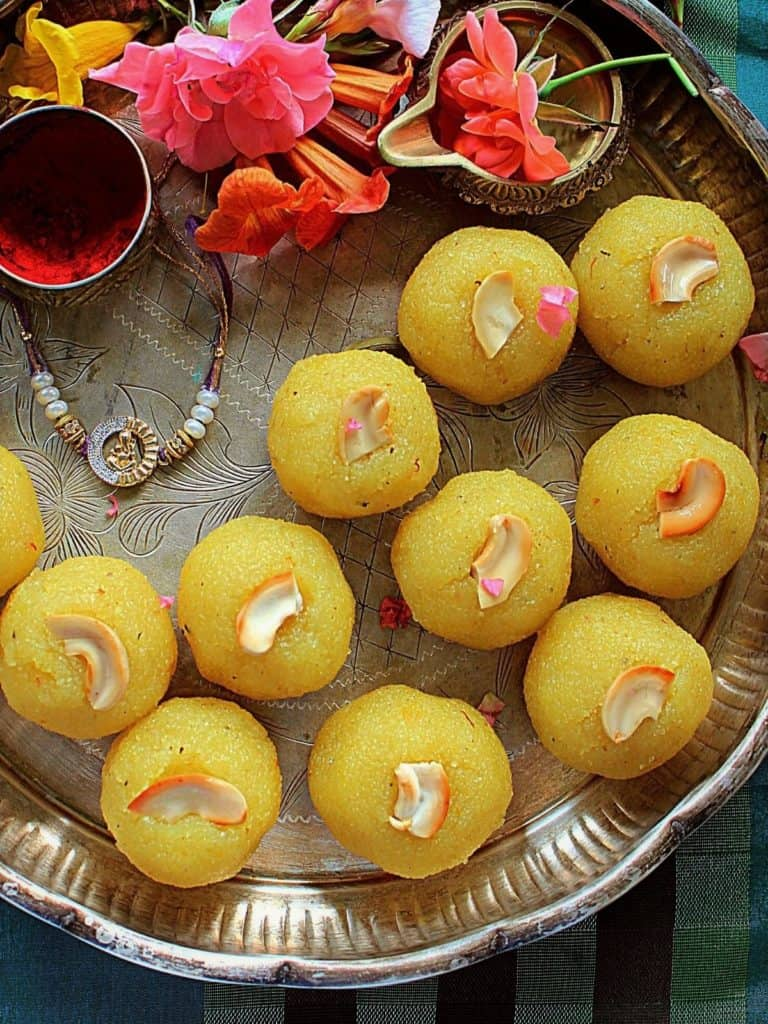 11 kesari bath ladoo placed in s silver plate with kukum and flowers and rakhi