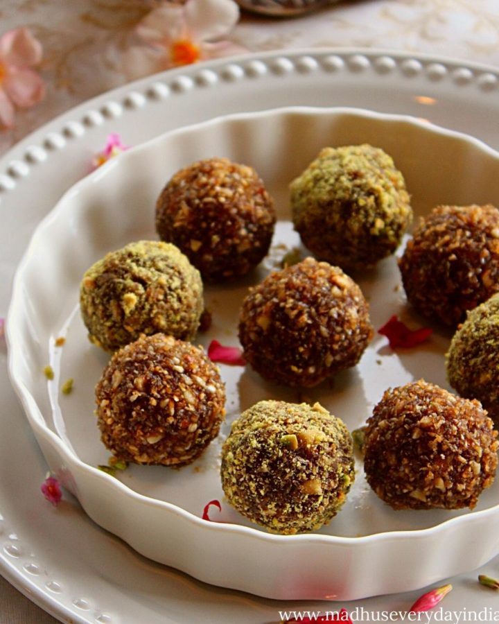 9 coconut nuts ladoo are arranged in a plate with rose petals