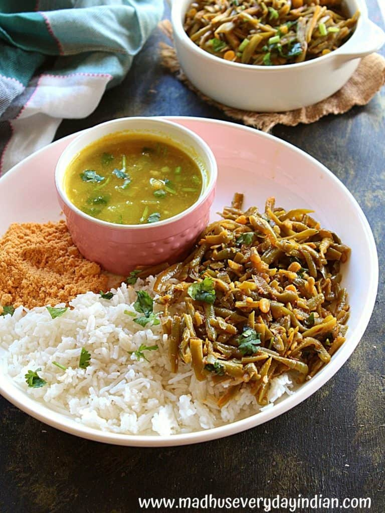 white rice, podi, dal and grozen french cut green poriyal served in a white plate