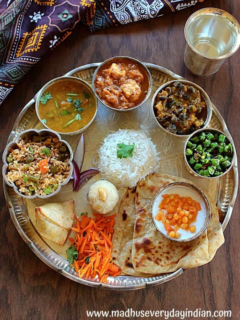 silver thali with rice, curries and rava ladoo