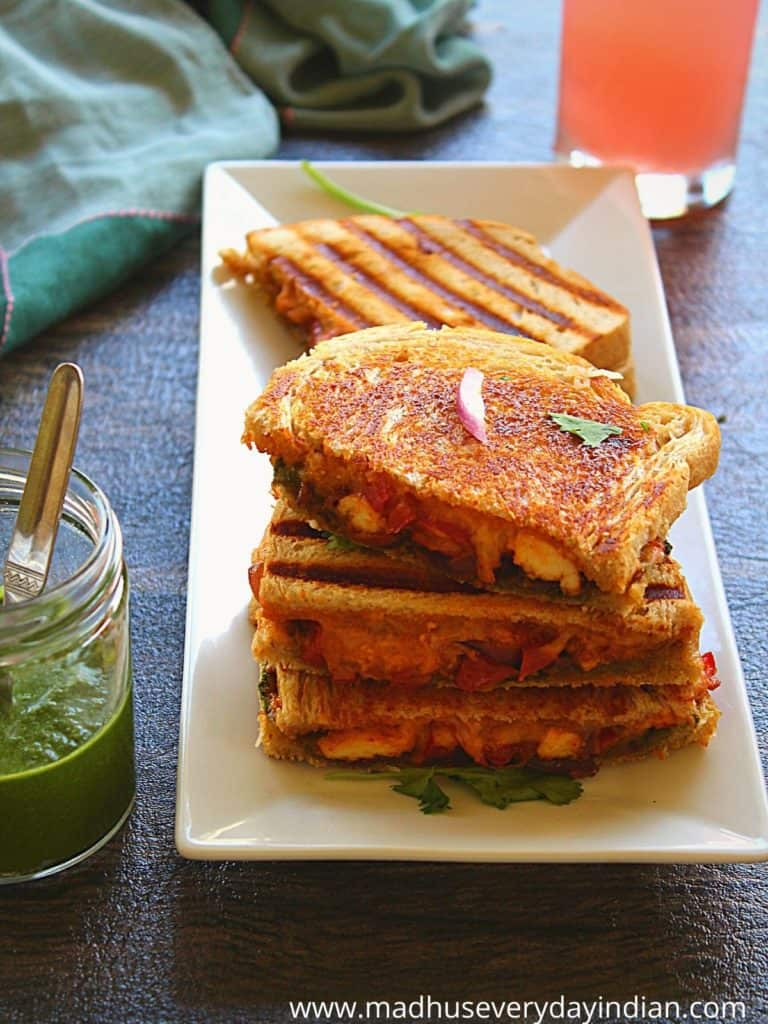 3 paneer sandwiches stacked on each other and served with green chutney