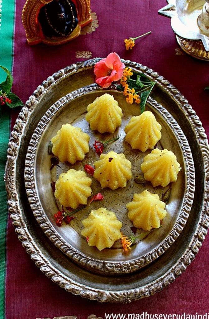 rava kesari modak arranged in a silver p;ate with flowers