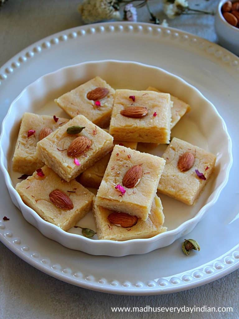 pieces of ricotta cheese badam burfi placed ina  white plate garnished with almonds and rose petals