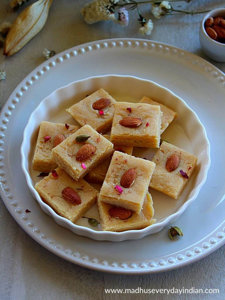 ricotta cheese almond flour burfi pieces arranged ina  white plate garnished with rose petals