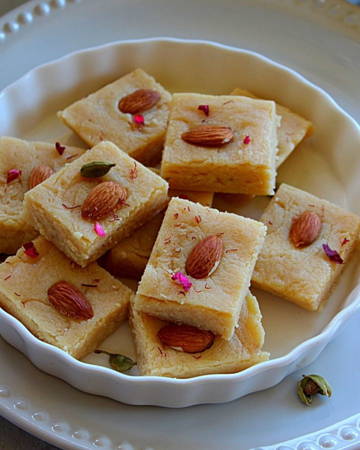 ricotta cheese and badam burfi served in a white plate