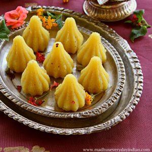 8 sooji halwa modak arranged in 2 silver paltes garnished with rose petals