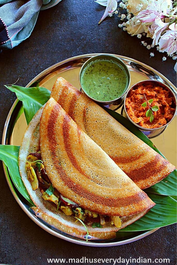 2 masala dosa served with chutneys is a steel plate